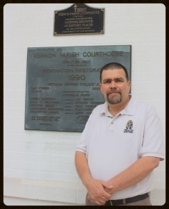Leesville Main Street Manager Sam Kincade stands in front of the plaque designating the Historic Vernon Parish Courthouse as having been added to the National Register of Historic Places. Kincade now serves on the committee that makes those designations for the state of Louisiana.