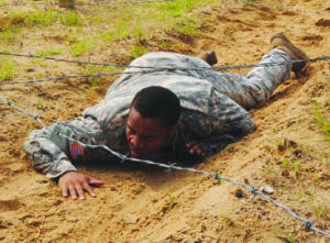 Sgt. Teren Morris, 383rd Modular Movement Control Team, 519th Military Police Battalion, low-crawls under barbed wire during the air assault obstacle course portion of the competition June 15.