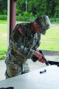 Spc. Joseph Rainger, Headquarters and Headquarters Company, U.S. Army Garrison, 5th Aviation Battalion, conducts a weapons check on the Beretta M9 pistol during the weapons proficiency portion of the competition June 15.
